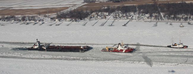 A U.S. Coast Guard cutter and Canadian Coast Guard ship assists a vessel through an icy waterway.  Lake Superior News